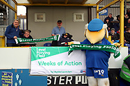Haydon the Womble holding up Level Playing Field scarf with AFC Wimbledon fans during the EFL Sky Bet League 1 match between AFC Wimbledon and Bolton Wanderers at the Cherry Red Records Stadium, Kingston, England on 7 March 2020.