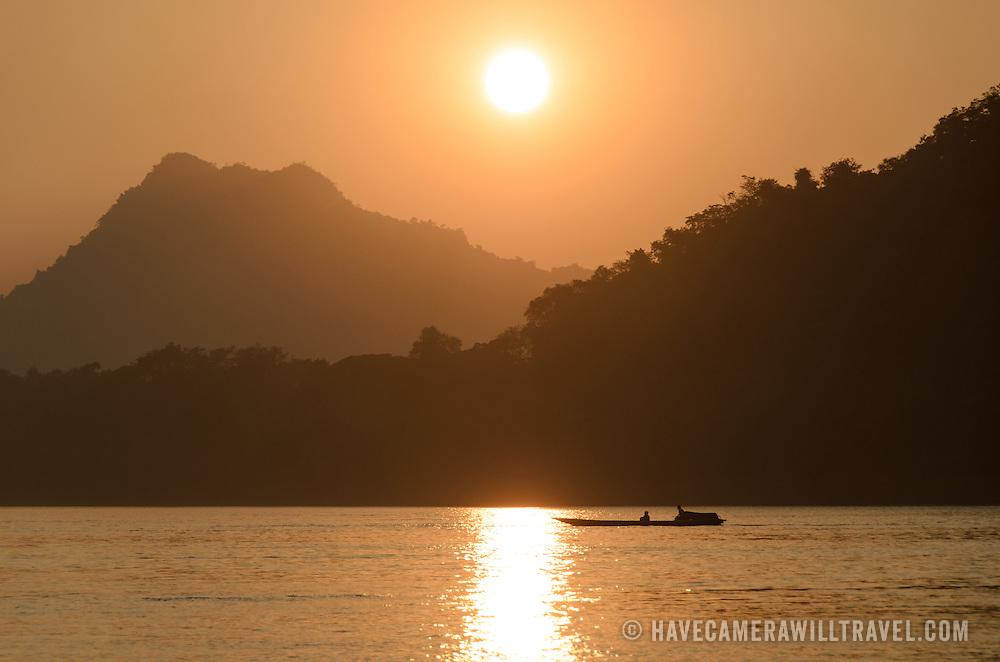 A lone small sampan crosses the river just before sunset on the Mekong River near Luang Prabang, Laos.