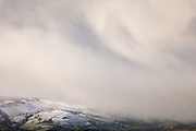 A phenomenal snow storm advancing along the Hope Valley and partially engulfing Shatton Moor. Dramatic winter scenes in the Derbyshire Peak District, England, UK.