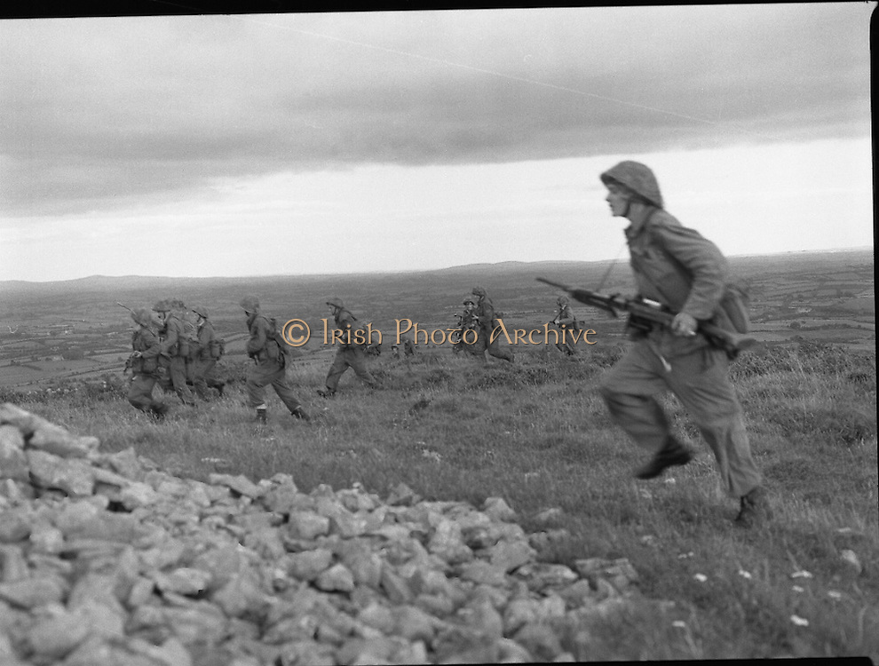 """Army Exercises In Co Sligo.   (L37).<br /> 1977.<br /> 05.09.1977.<br /> 09.05.1977.<br /> 5th September 1977.<br /> The Army Reserve Brigade, which is made up of regular units from the Southern Command, are conducting a series of conventional military exercises in counties Mayo and Sligo from the 5th to the 9th September. Approximately 1,500 men and 250 vehicles are involved. The exercise was codenamed """"Humbert"""" after an ill fated expedition by French troops into Ireland on 23rd August 1798. 1,100 French troops with Irish support took on the incumbent English forces. After some initial success they were defeated at Ballinamuk on 8th Sept 1798 by the army of Cornwallis.<br /> <br /> Soldiers are pictured advancing up the hillside in attack formation."""