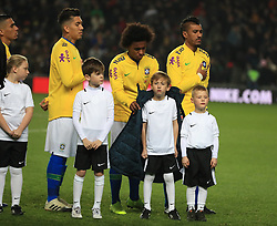 Brazil's Willian wraps a coat around a cold mascot during the anthems the international friendly match at Stadium MK, Milton Keynes.