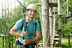 Portrait of young man climbing crag, smiling