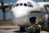 Padang,Western Sumatra, Indonesia, 9th October 2009: An Indonesian soldier watches a cargo plane arrive at a storage hanger at Padang airport which is being used to unload aid deliveries from around the world to earthquake devastated Western Sumatra follwoing the devastating earthquake in Western Sumatra that claimed the lives of an estimated 2000 people.?photo: Joseph Feil