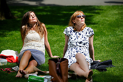 © Licensed to London News Pictures. 26/05/2016. London, UK. Finance workers Catherine Roberts and Kerri Scott enjoying sunshine and warm weather on their lunch breaks in Jubilee Park in Canary Wharf, London onThursday, 26 May 2016. Photo credit: Tolga Akmen/LNP