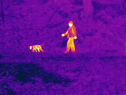 A Thermogram of a man walking a dog.  The different colors represent different temperatures on the object. The lightest colors are the hottest temperatures, while the darker colors represent a cooler temperature.  Thermography uses special cameras that can detect light in the far-infrared range of the electromagnetic spectrum (900?14,000 nanometers or 0.9?14 µm) and creates an  image of the objects temperature..