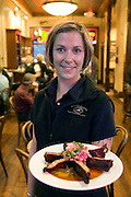 Bounty Hunter Restaurant and Bar, Napa, California. Napa Valley. Waitress Heather Renfrow with barbecued ribs with cole slaw. MODEL RELEASED.