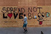 A passerby walks past a sign on State Street in downtown Madison June 5th. (Photo © Andy Manis)