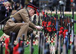 © Licensed to London News Pictures. 10/11/2011. London, UK. A serving soldier hammers in a cross. HRH The duke of Edinburgh opens the annual Field of Remembrance at Westminster Abbey today 10 November. . Photo credit : Stephen Simpson/LNP