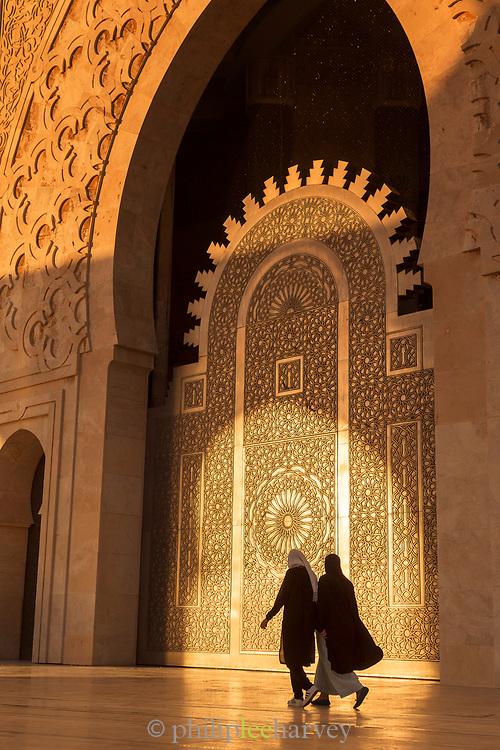 Rear view of two women walking nearby Hassan II Mosque in Casablanca, Morocco