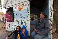 """FOTO DE GRUPO DE LA ASISTENTE SOCIAL GLADYS CON ALGUNOS NINOS DEL """"APOYO ESCOLAR DULCE ESPERANZA"""" JUEGAN EN EL JARDIN DEL COMEDOR """"TODOS JUNTOS"""", DIQUE LUJAN, PROVINCIA DE BUENOS AIRES, ARGENTINA ((PHOTO © MARCO GUOLI - ALL RIGHTS RESERVED)"""