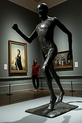 "© Licensed to London News Pictures. 05/06/2018. LONDON, UK. (L) ""Queen Elizabeth II"", 1955, by Pietro Annigoni and a sculpture ""The Running Man"", 1978, by Dame Elisabeth Frink at a preview of the 250th Summer Exhibition at the Royal Academy of Arts in Piccadilly, which has been co-ordinated by Grayson Perry RA this year.  Running concurrently, is The Great Spectacle, featuring highlights from the past 250 years.  Both shows run 12 June to 19 August 2018.  Photo credit: Stephen Chung/LNP"
