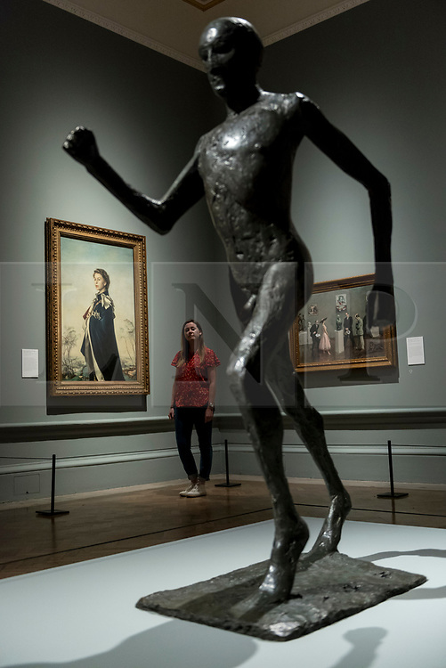 """© Licensed to London News Pictures. 05/06/2018. LONDON, UK. (L) """"Queen Elizabeth II"""", 1955, by Pietro Annigoni and a sculpture """"The Running Man"""", 1978, by Dame Elisabeth Frink at a preview of the 250th Summer Exhibition at the Royal Academy of Arts in Piccadilly, which has been co-ordinated by Grayson Perry RA this year.  Running concurrently, is The Great Spectacle, featuring highlights from the past 250 years.  Both shows run 12 June to 19 August 2018.  Photo credit: Stephen Chung/LNP"""