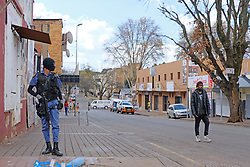 JOHANNESBURG, SOUTH AFRICA - APRIL 18: A SAPS officer and member of the public during a South African Police Service (SAPS) Metro Police and Army supported patrol in Rockey Street, Yeoville. Random searchs and social distancing measures on April 18, 2020 in Johannesburg South Africa. Under pressure from a global pandemic. President Ramaphosa declared a 21 day national lockdown extended by another two weeks, mobilising goverment structures accross the nation to combat the rapidly spreading COVID-19 virus - the lockdown requires businesses to close and the public to stay at home during this period, unless part of approved essential services. (Photo by Dino Lloyd)