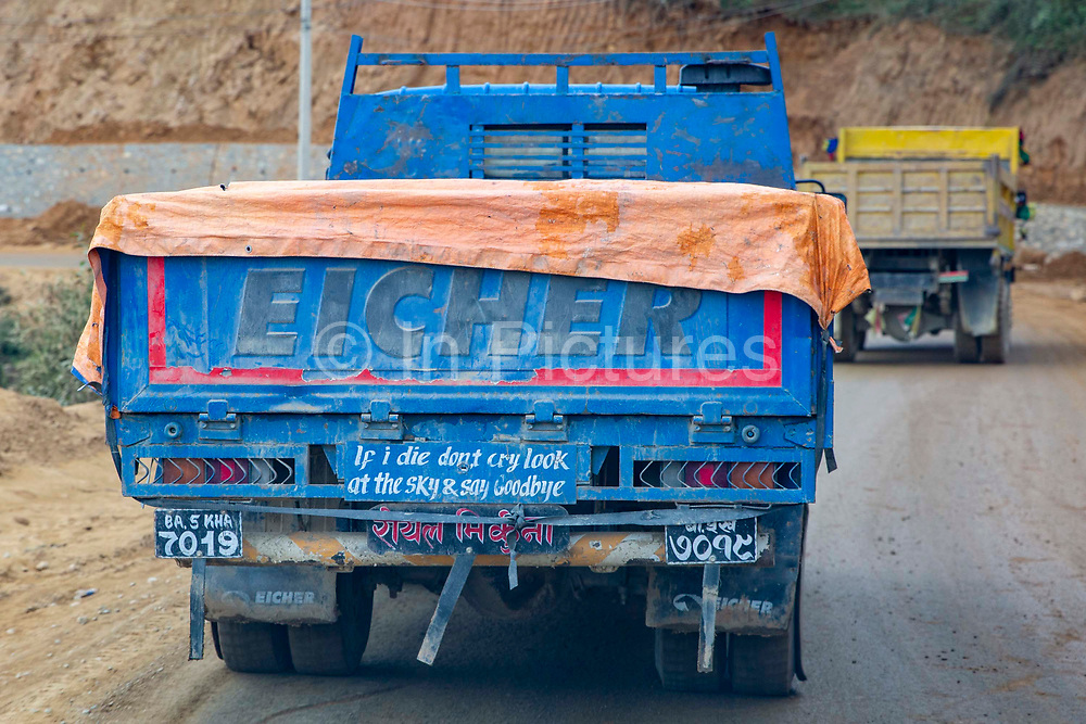 A Nepalese Eicher truck driving along the Satdobato-Tikabhairab Road on the13th of March 2020 in Lalitpur, Kathmandu District, Bagmati Pradesh, Nepal. The slogan 'If I die don't cry look at the sky & say goodbye' is painted on the back. Many nepalese trucks have slogans or sayings painted on the back.