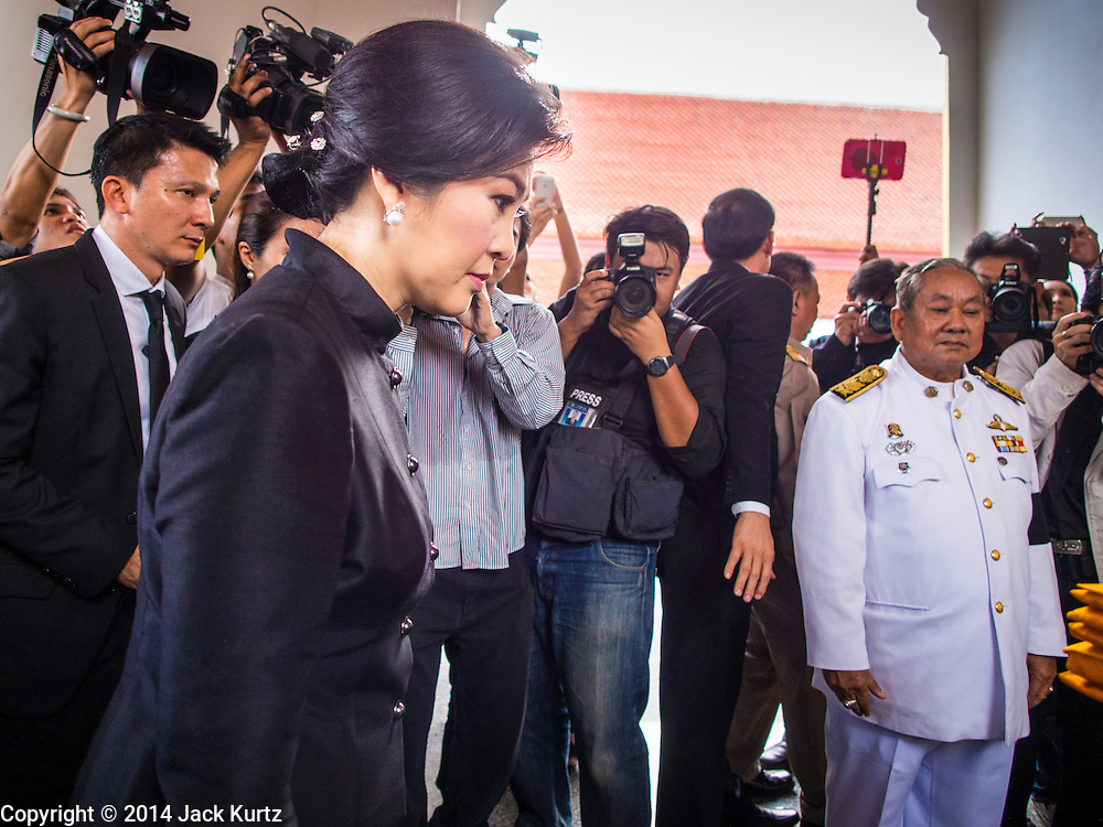 19 OCTOBER 2014 - BANG BUA THONG, NONTHABURI, THAILAND: YINGLUCK SHINAWATRA, former Prime Minister of Thailand, (left) mourns at Apiwan Wiriyachai's cremation at Wat Bang Phai in Bang Bua Thong, a Bangkok suburb, Sunday. Apiwan was a prominent Red Shirt leader. He was member of the Pheu Thai Party of former Prime Minister Yingluck Shinawatra, and a member of the Thai parliament and served as Yingluck's Deputy Prime Minister. The military government that deposed the elected government in May, 2014, charged Apiwan with Lese Majeste for allegedly insulting the Thai Monarchy. Rather than face the charges, Apiwan fled Thailand to the Philippines. He died of a lung infection in the Philippines on Oct. 6. The military government gave his family permission to bring him back to Thailand for the funeral. His cremation was the largest Red Shirt gathering since the coup.     PHOTO BY JACK KURTZ