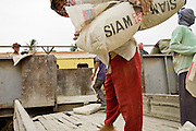 30 JUNE 2006 - PHNOM PENH, CAMBODIA: Workers unload cement from Thailand from a freight train in the Phnom Penh train station. While much of Cambodia's infrastructure has been rebuilt since the wars which tore the country apart in the late 1980s, the train system is still in disrepair. There is now only one passenger train in the country. It runs from Phnom Penh to the provincial capitol Battambang and it runs only one day a week. It takes 12 hours to complete the 190 mile journey.  Photo by Jack Kurtz / ZUMA Press