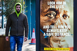 """© Licensed to London News Pictures. 29/01/2021. London, UK. A man without wearing a protective face covering walks past the government's 'Look him in the eyes - And tell him you always keep a safe distance.' publicity campaign poster in north London. Covid-19 infection rates are continuing to drop across London. But health experts are warning Londoners to follow the lockdown rules, as """"any relaxation would risk a rapid reversal or decline."""" Photo credit: Dinendra Haria/LNP"""