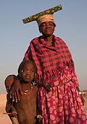 A Herero mother dressed in traditional clothes poses with her children in Opuwo, Namibia, Africa.