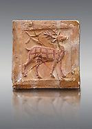 6th-7th Century Eastern Roman Byzantine  Christian Terracotta tiles depicting a stag - Produced in Byzacena -  present day Tunisia. <br /> <br /> The stag is a traditional Christian symbol for Christ, Who tramples and destroys the Devil. In the Medieval bestiaries the stag as an enemy of snakes. It was believed that stags was believed to chase snakes into their holes or rock crevices, driving them out by flooding the hole with the breath or water from its mouth, and eating them. <br /> <br /> These early Christian terracotta tiles were mass produced thanks to moulds. Their quadrangular, square or rectangular shape as well as the standardised sizes in use in the different regions were determined by their architectonic function and were designed to facilitate their assembly according to various combinations to decorate large flat surfaces of walls or ceilings. <br /> <br /> Byzacena stood out for its use of biblical and hagiographic themes and a richer variety of animals, birds and roses. Some deer and lions were obviously inspired from Zeugitana prototypes attesting to the pre-existence of this province's production with respect to that of Byzacena. The rules governing this art are similar to those that applied to late Roman and Christian art with, in the case of Byzacena, an obvious popular connotation. Its distinguishing features are flatness, a predilection for symmetrical compositions, frontal and lateral representations, the absence of tridimensional attitudes and the naivety of some details (large eyes, pointed chins). Mass production enabled this type of decoration to be widely used at little cost and it played a role as ideograms and for teaching catechism through pictures. Painting, now often faded, enhanced motifs in relief or enriched them with additional details to break their repetitive monotony.<br /> <br /> The Bardo National Museum Tunis, Tunisia.   Against a grey background.