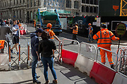 Construction workers temporarily close Lombard Street to pedestrians as a skip lorry exits their site, in the heart of the capitals financial district, on 19th April, in the City of London, England.