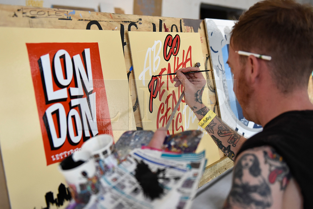 """© Licensed to London News Pictures. 17/08/2018. LONDON, UK. A sign writer practices at """"Letterheads 2018: London Calling"""", an international gathering of professional sign writers and lettering artists from over 30 countries.  The event is taking place at the Bargehouse, Oxo Tower Wharf in central London untikl 19 August.  Photo credit: Stephen Chung/LNP"""