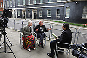 Dame Vivienne Westwood and son Joe Corre from Talk Fracking bring 'armagedddon' to to Downing Street June 5th 2018, Central London, United Kingdom. TV interview in Downing Street. The  protest is  against the petro chemical company INEOS' license to frack. They say 'Planet Ineos will destroy us all in quest to frack for plasctic'. INEOS produces plasctic and is currently using imported gas to the production and much of the gas they will be fracking may be used in the plastic industry.