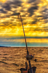 An early morning bite on the fishing line while boating in Lake Superior just after sunrise while the sun was peeking through the dark billowing clouds.