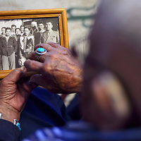 Samuel Sandoval looks at a photo from 1943 of himself and the fellow Navajo Code Talkers who graduated from basic training together pointing out the names of all of his old friends during an interview at his home in Shiprock February 21.