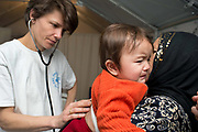 Greece . Chios Island, one of the places where refugees from Turkey land en route to Northern Europe. Souda camp. British doctor Dr Sophie Quinney examines Afghan baby Ashrafi.