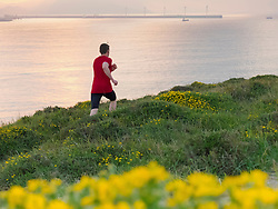 Rear view of man trail running in front of port of Bilbao
