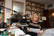 """March 6, 2015, Paris, France. Writer Maryse Wolinski (1943, Algiers) working at her desk, in the Paris' apartment where Georges and Maryse Wolinski used to live. Two month after the death of Georges Wolinski, the apartment is full of souvenirs and notes, attesting a half-century-long love relation. In 2016 Maryse Wolinski published the book """"Chérie, je vais à Charlie"""" about her husband and the attack on Charlie Hebdo. The cartoonist Georges Wolinski was 80 years old when he was murdered by the French jihadists Chérif en Saïd Kouachi, he was one of the 12 victims of the massacre in the Charlie Hebdo offices on January 7, 2015 in Paris. Charlie Hebdo published caricatures of Mohammed, considered blasphemous by some Muslims. During his life, Georges Wolinski defended freedom, secularism and humour and was one of the major political cartoonists in France. The couple was married and had lived for 47 years together. Photo: Steven Wassenaar."""
