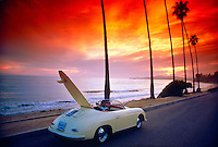 Porsche Speedster with surfboard at sunset along  the coastal road in Montecito, California USA (Pacific Ocean in background)