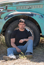 hot man with green eyes and dark hair sitting against a pickup truck