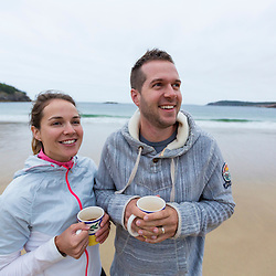 A couple drinking coffee on a cloudy morning at Sand Beach in Maine's Acadia National Park.