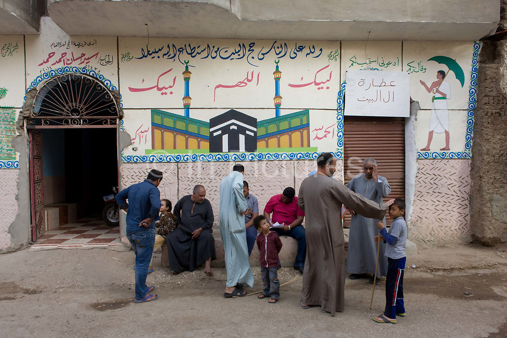 Neighbours hold an informal meeting under Islamic murals in a street of the village of Bairat on the West Bank of Luxor, Nile Valley, Egypt. Many of these people are dependent of the tourism industry and therefore badly affected by the downturn. According to the country's Ministry of Tourism, European visitors to Egypt is down by up to 80% in 2016 from the suspension of flights after the downing of the Russian airliner in Oct 2015. Euro-tourism accounts for 27% of the total flow and in total, tourism accounts for 11.3% of Egypt's GDP so communities like this are suffering economically, as a result.