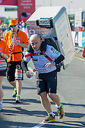Man with a fridge. The London Marathon starts in Greenwich on Blackheath passes through Canary Wharf and finishes in the Mall. London UK, 13 April 2014.  Guy Bell, 07771 786236 guy@gbphotos.com