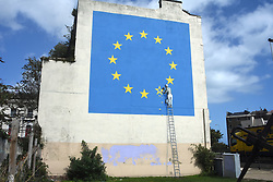 October 2017, Dover, UK. Art work of Banksy in Dover depicting worker chisling away one of the stars of the European Union, symbolizing the Brexit. (Photo by Teun Voeten/Sipa USA)