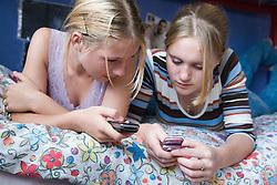 Teenage girls looking at their mobile phones in their bedroom,