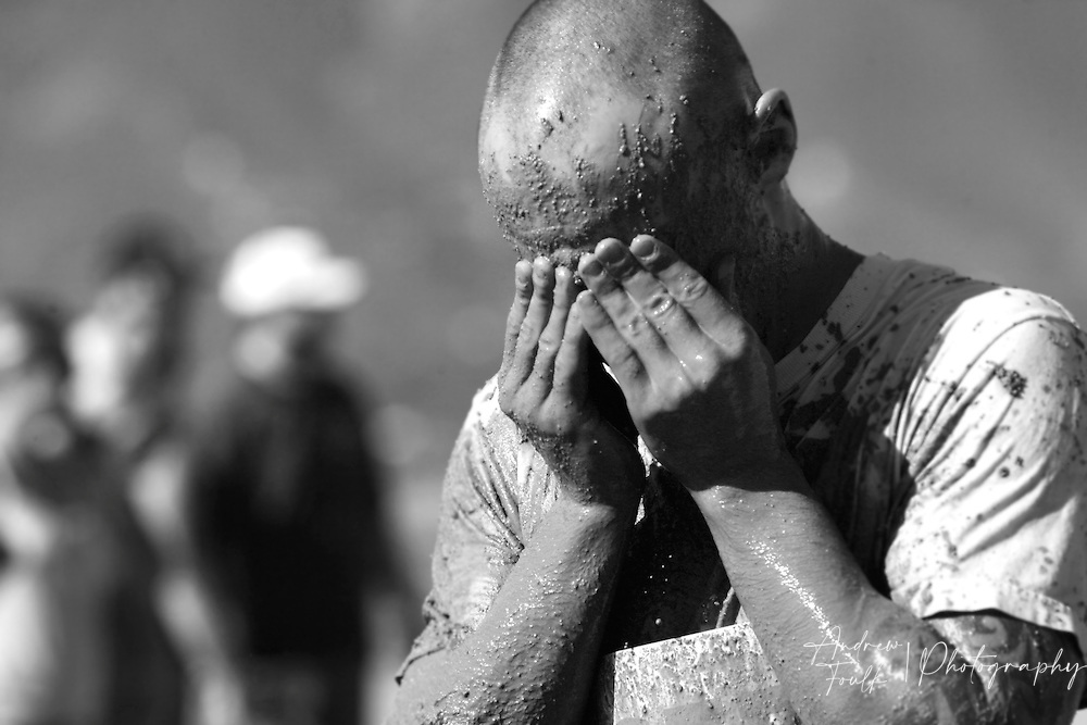 /Andrew Foulk/ For The Californian/ .A competitor in the Lake Elsinore Gladiator Run, wipes mud from his face after going through the mud pit during the 5K run.