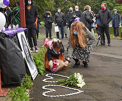 Pictured: A little girl lays flowers during the vigil.<br /> <br /> Friends and supporters held a vigil in Govan in memory of tragic asylum seeker Mercy Baguma, who was found dead next to her baby son on 22nd August at a flat in the city.<br /> <br /> © Dave Johnston / EEm