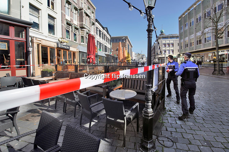Nederland, Nijmegen, 22-3-2020  Om te voorkomen dat bezoekers aan de binnenstad op de lege terrassen gaan zitten  spannen medewerkers van bureau toezicht op aanwijzing van burgemeester Hubert Bruls afzetlint voor de tarrassen. Foto: Flip Franssen