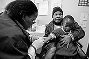 Lucy Tseka, a nurse, takes the blood of Rapalo Mokhatholane, 8, being held by his aunt Matsolo Hlaoli. The Teyateyaneng Hospital (Lesotho) ARV Clinic sees and monitors HIV positive patients and is jam-packed everyday.