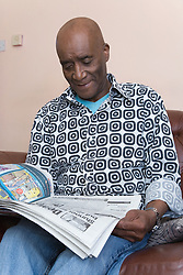 Older man at home reading the paper,
