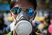 """01 DECEMBER 2013 - BANGKOK, THAILAND: An anti-government protestor with his """"gas mask"""" and """"goggles."""" Thousands of anti-government Thais confronted riot police at Phanitchayakan Intersection, where Rama I and Phitsanoluk Roads intersect, next to Government House (the office of the Prime Minister). Protestors threw rocks, cherry bombs, small explosives and Molotov cocktails at police who responded with waves of tear gas and chemical dispersal weapons. At least four people were killed at a university in suburban Bangkok when gangs of pro-government and anti-government demonstrators clashed. This is the most serious political violence in Thailand since 2010.    PHOTO BY JACK KURTZ"""