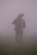 Photographer Stephen Kirkpatrick headed out to shoot, walking across a field on a foggy morning - Mississippi