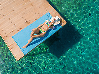 Aerial view of attractive woman wearing white hat sunbathing on wooden pontoon in Panagopoula, Greece.