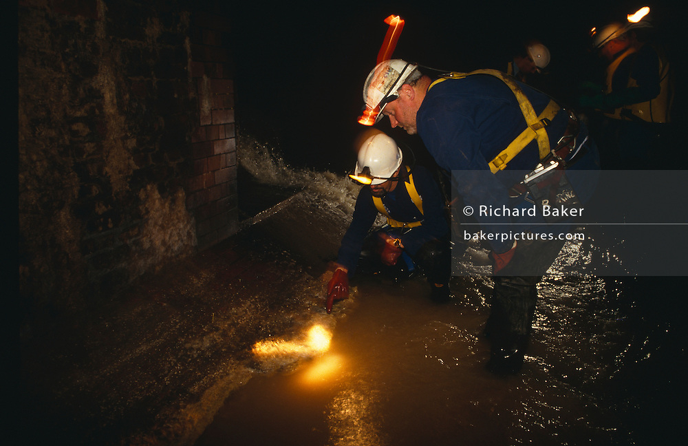 Thames Water Utilities sewer cleaning team inspects the Fleet River's Victorian-built storm sewer of Blackfriars, beneath the streets of the City of London. Discarded fats from restaurants congeal in sewer networks leading to blocked pipework. Sewer men are shovel the deposits and bring them in vats to the surface. In the early 19th century the River Thames was practically an open sewer, with disastrous consequences for public health in London, including numerous cholera epidemics with the The Great Stink of 1858 a turning point. Intercepting sewers constructed between 1859 and 1865 were fed by 450 miles (720 km) of main sewers that in turn conveyed the contents of some 13,000 miles (21,000 km) of smaller local sewers using 318m bricks, 880,000 cubic yards of concrete and mortar and excavation of over 3.5m tonnes of earth.