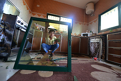 June 26, 2017 - Gaza, Gaza strip, Palestine - A Palestinian boy removes broken glass from his window following an Israeli air strike in Gaza City on June 27, 2017. Israeli airstrikes hit a series of targets in the Hamas-run Gaza Strip overnight June 26, officials said, hours after a rocket from the Palestinian enclave landed in the Jewish state. (Credit Image: © Majdi Fathi/NurPhoto via ZUMA Press)