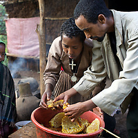 "While their daughter Rekebki looks on, Wubalem and her husband Tsega clean the honey and wax harvested from a traditional hive. This is a much more labourious task than processing the honey from modern hives. <br /> <br /> Wubalem Shiferaw, age 23, lives in the village of Mecha with her husband Tsega Bekele, age 33, and their daughter Rekebki, age 4. Wubalem remembers her grandparents harvesting honey. She has maintained this tradition while moving to modern hives which produce a far greater yield of honey. Wubalem is a member of the Mecha village Cooperative which brings together local women beekeepers allowing them to share insights and build a credit union. The Mecha village Cooperative is not yet a member of the Zembaba Union. Wubalem's husband Tsega is a priest and a tailor. <br /> <br /> Harvesting honey supplements the income of small farmers in the Ethiopian region of Amhara where there is a long tradition of honey production. However, without the resources to properly invest in production and the continued use of of traditional, low-yielding hives, farmers have not been able to reap proper reward for their labour. <br /> <br /> The formation of the Zembaba Bee Products Development and Marketing Cooperative Union is an attempt to realize the potential of honey production in Amhara and ensure that the benefits reach small producers. <br /> <br /> By providing modern, high-yield hives, protective equipment and training to beekeepers, the Cooperative Union helps increase production and secure a steady supply of honey for which there is growing demand both in and beyond Ethiopia. The collective processing, marketing and distribution of Zembaba's ""Amar"" honey means that profits stay within the cooperative network of 3,500 beekeepers rather than being passed onto brokers and agents. The Union has signed an agreement with the multinational Ambrosia group to supply honey to the export market. <br /> <br /> Zembaba Bee Products Development and Marketing Cooperative Union also provides credit to individual members and trains c"