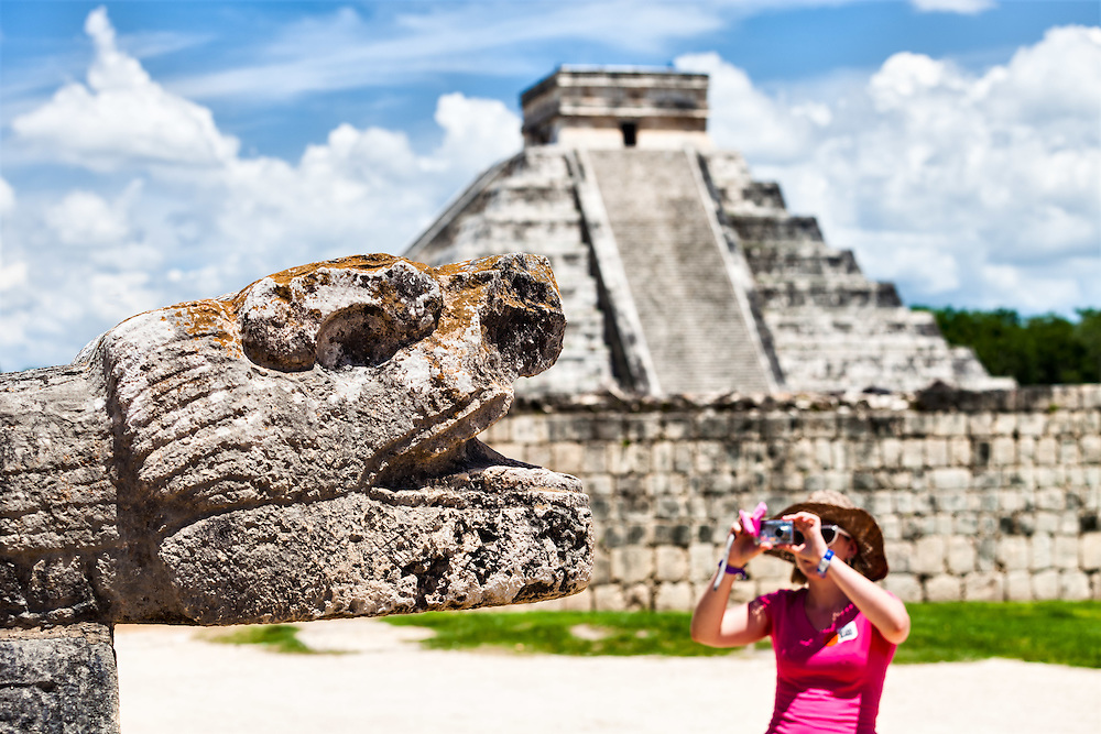 Chichen Itza, tourist photographing the snake head with the pyramid El Castillo in the background, Yucatan, Mexico